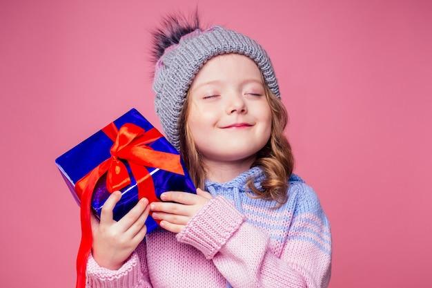 Szczęśliwa mała uśmiechnięta blondynka kręcone fryzury dziewczyna w dzianym szarym kapeluszu z świątecznym pudełkiem z kokardą na różowym tle studio. nowy rok obecny w rękach dziecka płci żeńskiej co życzenie copyspace.