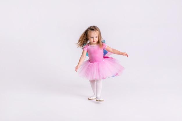 Szczęśliwa mała zabawna emocjonalna dziewczyna dziecko w ładny różowy kucyk kostium na białym kolorowym tle.