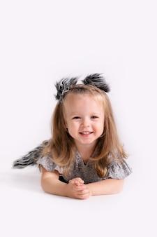 Szczęśliwa mała zabawna emocjonalna dziewczynka dziecko w stroju ładny wilk na białym kolorowym tle.