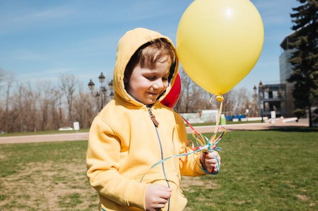 Szczęśliwa małe dziecko chłopiec chodzi outdoors w parku z balonami