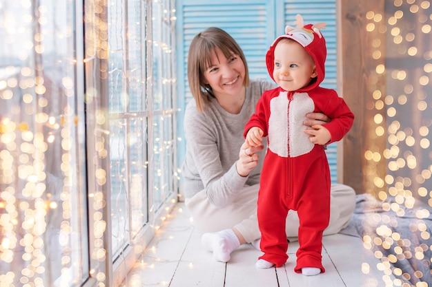 Szczęśliwa mama bawi się z maluchem w czerwonym stroju jelenia na tle okna i girland świetlnych