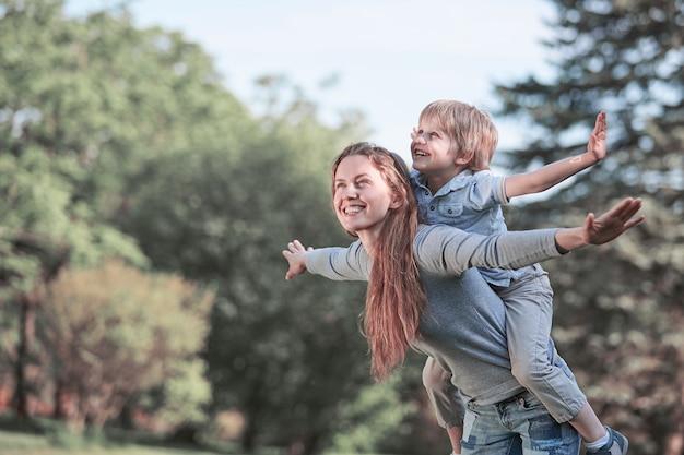 Szczęśliwa mama bawi się z synem w letnim parku