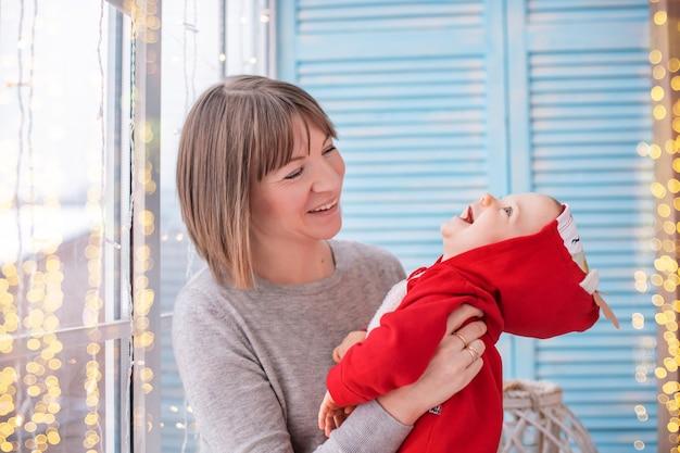 Szczęśliwa mama bawi się ze swoim maluchem w czerwonym stroju jelenia na tle okna i girland świetlnych