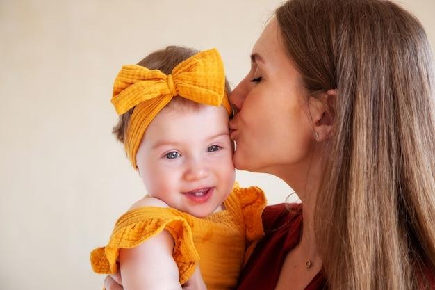 Szczęśliwa mama całuje swoją roczną córkę w żółtych ubraniach, studio fotograficzne na rok dziecka