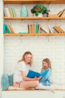 Szczęśliwa mama czyta córce wesołą bajkę w książce i uśmiecha się siedząc w salonie