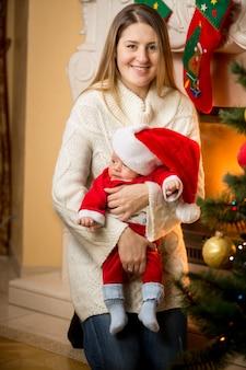 Szczęśliwa mama i chłopczyk w stroju świętego mikołaja w wigilię bożego narodzenia
