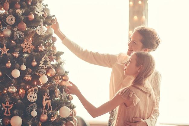 Szczęśliwa mama i córeczka dekorują choinkę