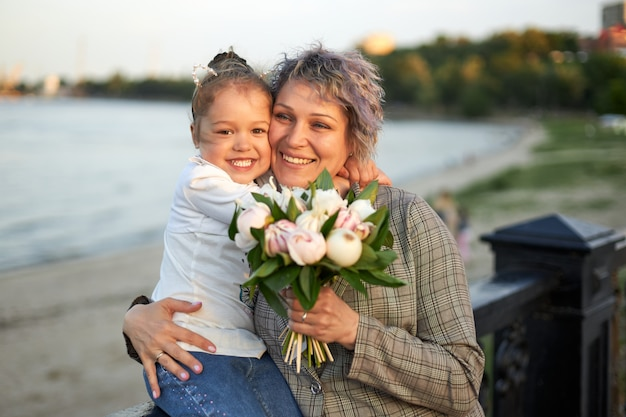 Szczęśliwa mama i córeczka stoją wieczorem na miejskiej promenadzie i śmieją się