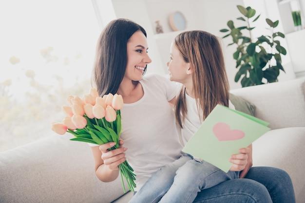 Szczęśliwa mama i córka córka świętują marsz trzymają kartę bukietową w salonie