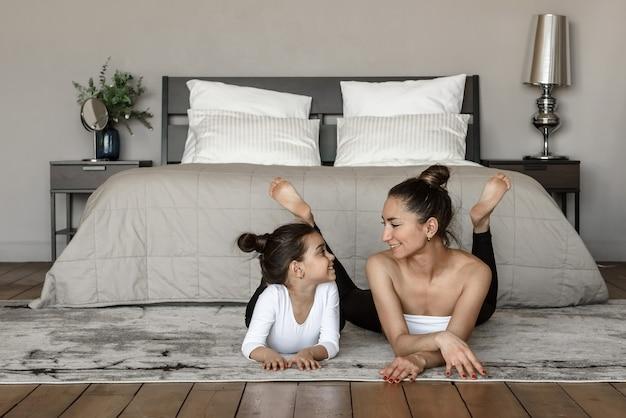 Szczęśliwa mama i córka dziecko leżą razem na podłodze, patrząc na siebie