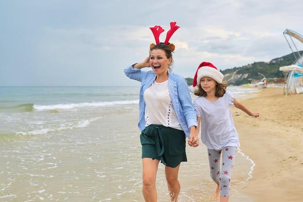 Szczęśliwa mama i córka dziecko w santa hat spaceru trzymając się za ręce wzdłuż plaży