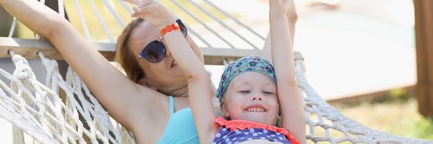 Szczęśliwa mama i córka jeżdżą w strojach kąpielowych na hamaku