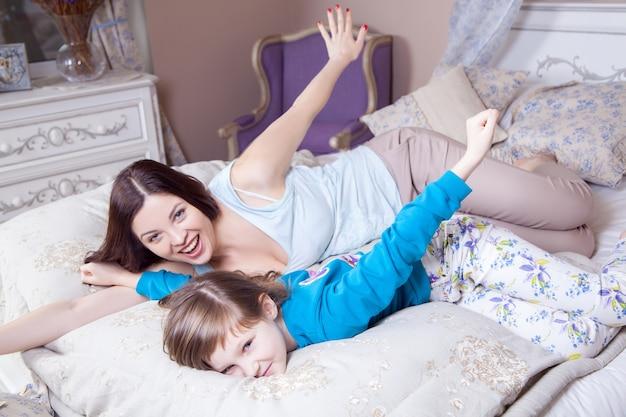 Szczęśliwa mama i córka obudziły się i bawiły się rano w piżamie na łóżku, śmiejąc się i uśmiechając. dobry humor. strzał studio.