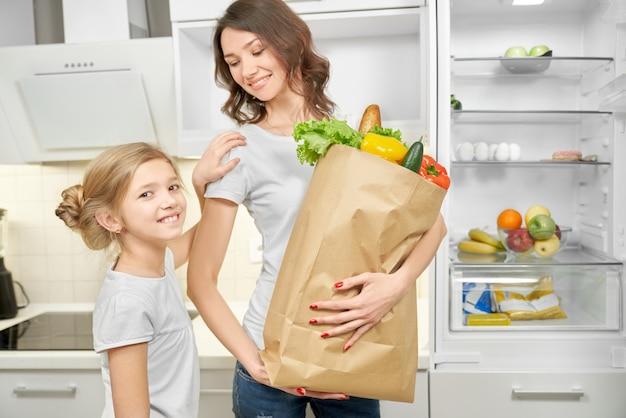 Szczęśliwa mama i córka pozuje z papierową torbą z produktami.