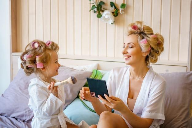 Szczęśliwa mama i córka robią makijaż siedząc na łóżku w sypialni