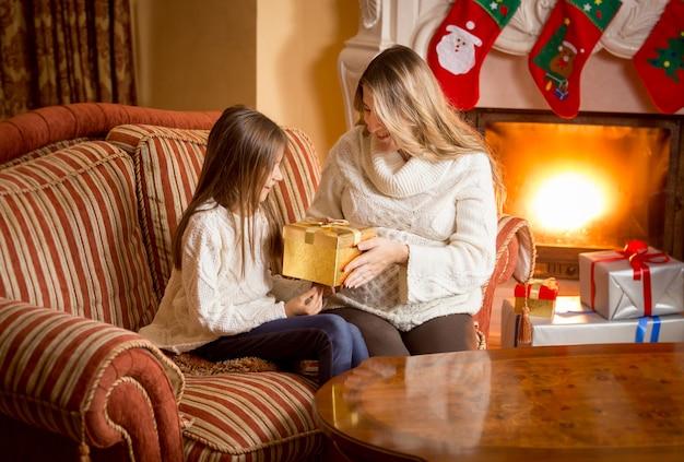 Szczęśliwa mama i córka rozpakowujące prezent świąteczny przy kominku