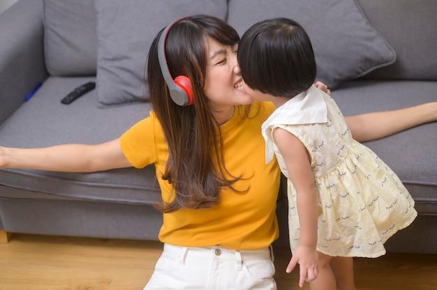 Szczęśliwa mama i córka słuchają muzyki i odpoczywają w domu