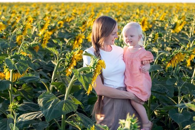 Szczęśliwa mama i córka w polu słoneczników. czułość i troska.