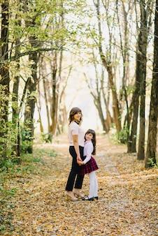Szczęśliwa mama i córka zakochują się w parku, trzymając się za ręce i uśmiechając się