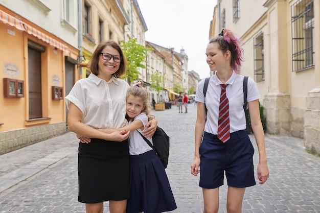 Szczęśliwa mama i córki idą do szkoły