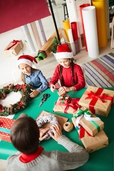 Szczęśliwa mama i córki pakujące prezenty świąteczne