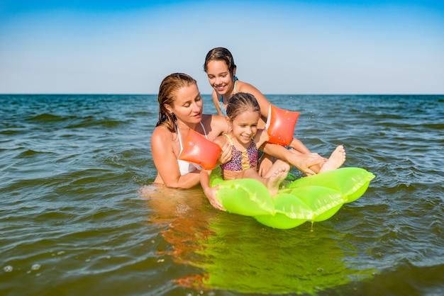Szczęśliwa mama i dwie małe pozytywne córki kąpią się i pływają w morzu z dmuchanym materacem w słoneczny letni dzień. koncepcja wakacji z dziećmi. copyspace