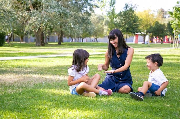 Szczęśliwa mama i dwoje dzieci siedzi na trawie w parku i gra. wesoła mama i dzieci spędzające wolny czas latem. koncepcja rodziny na zewnątrz
