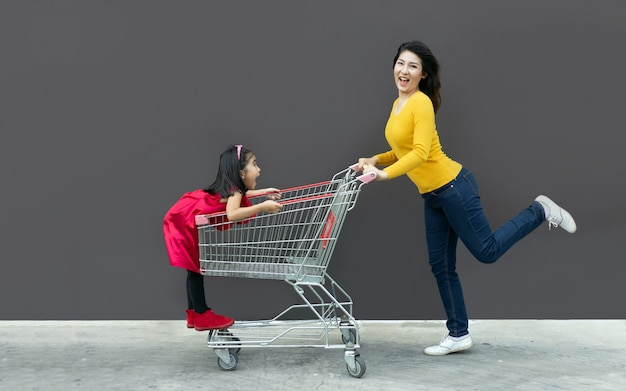 Szczęśliwa mama i dzieciak iść wózek na zakupy wpólnie