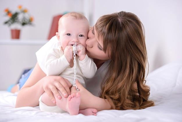 Szczęśliwa mama i dziecko bawić się na łóżku w domu.