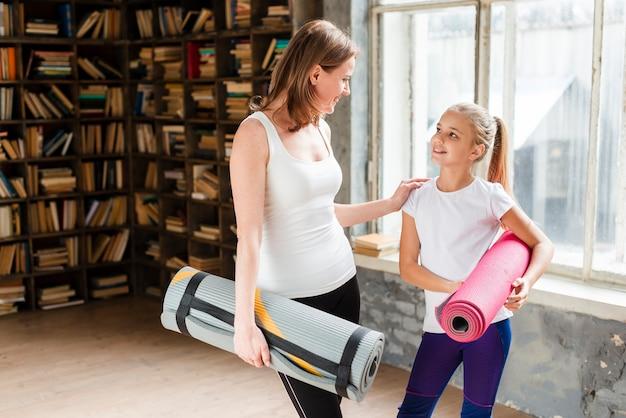 Szczęśliwa mama i dziewczyna trzyma maty do jogi