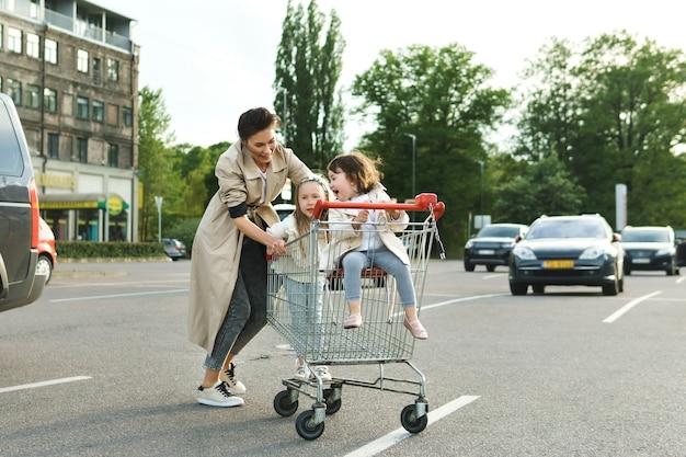 Szczęśliwa mama i jej córki bawią się wózkiem na zakupy