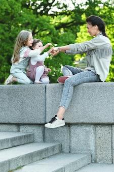 Szczęśliwa mama i jej dwie córki siedzą i bawią się w miejskim parku