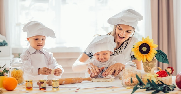 Szczęśliwa mama i jej dzieci robią ciasteczka w kuchni