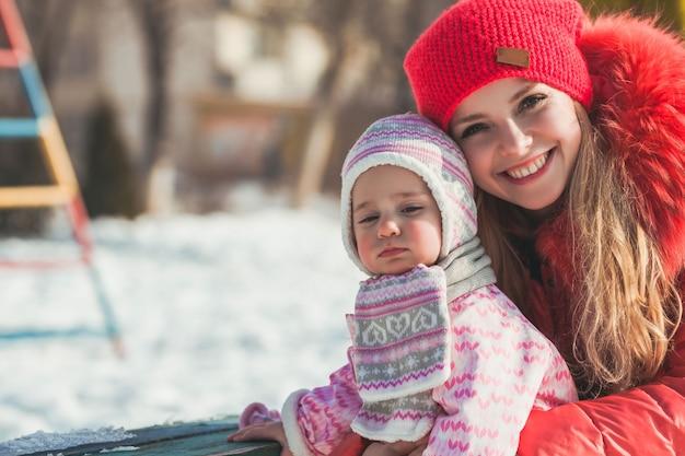 Szczęśliwa mama i mała dziewczynka spacerują w pobliżu ławki w parku zimowym i dobrze się bawią