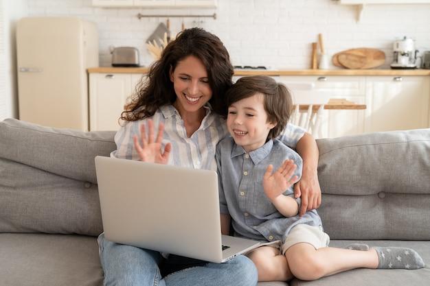 Szczęśliwa mama i syn używają połączenia wideo, aby zadzwonić do dziadków lub taty podczas podróży służbowej, machając rękami