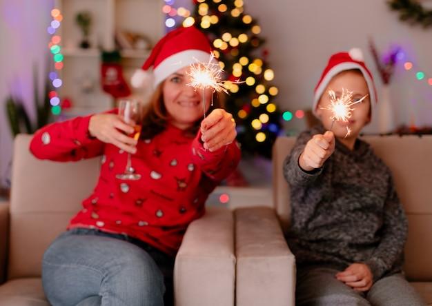 Szczęśliwa mama i synek w czapkach mikołaja z zimnymi ogniami siedzą na kanapie i bawią się w udekorowanym pokoju z choinką w tle
