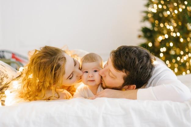 Szczęśliwa mama i tata leżą na łóżku obok swojego dziecka na tle lampek choinkowych i całują go