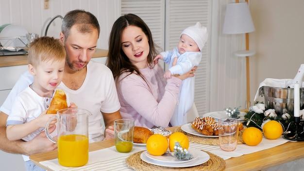 Szczęśliwa mama, ojciec i syn jedzą śniadanie w domu
