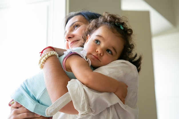 Szczęśliwa mama przytulanie i trzymając w ramionach córeczkę słodkie. śliczne kręcone włosy dziewczynka patrząc na matkę. koncepcja rodzicielstwa i dzieciństwa