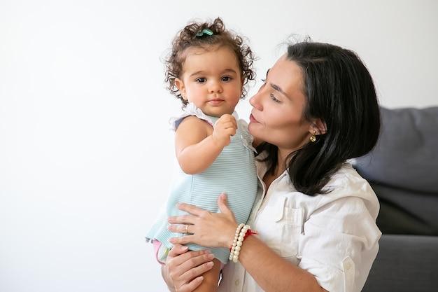 Szczęśliwa mama trzyma w ramionach słodką córeczkę. śliczna mała dziewczynka. skopiuj miejsce. koncepcja rodzicielstwa i dzieciństwa
