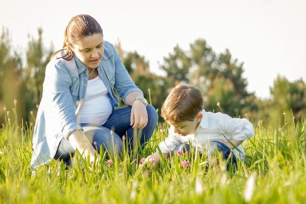 Szczęśliwa mama w ciąży i uroczy syn zbierają bukiet kwiatów na słonecznym polu
