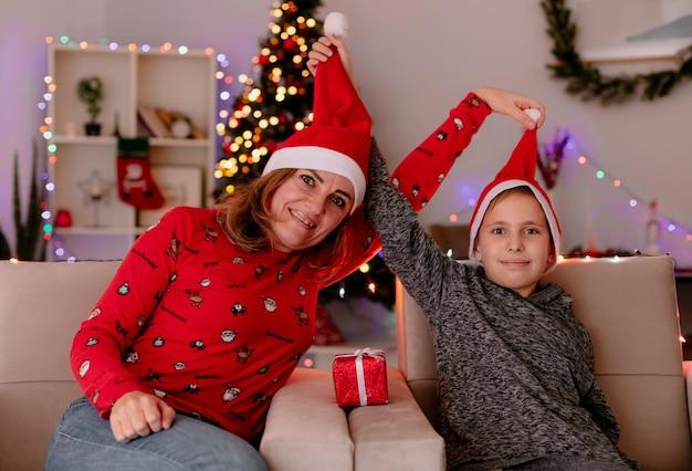 Szczęśliwa mama w czapce mikołaja i synek w czapce mikołaja z prezentem siedzi na kanapie bawiąc się w udekorowanym pokoju z choinką w ścianie