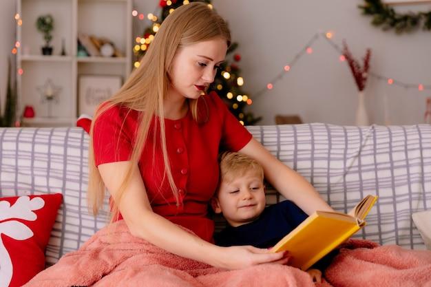 Szczęśliwa mama w czerwonej sukience z małym dzieckiem pod kocem z książką czytającą w udekorowanym pokoju z choinką na ścianie