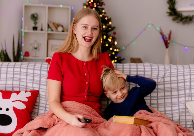 Szczęśliwa mama w czerwonej sukience z pilotem do telewizora i jej małym dzieckiem pod kocem z książką w udekorowanym pokoju z choinką w ścianie