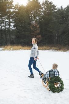 Szczęśliwa mama w dzianinowym swetrze i dżinsach niesie swojego małego synka na drewnianych saniach