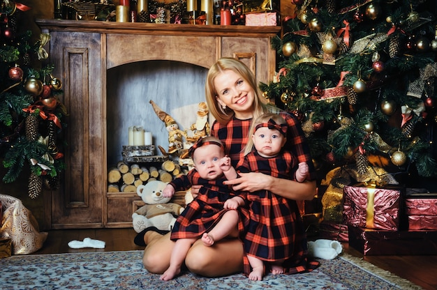 Szczęśliwa mama z bliźniakami w noworocznym wnętrzu domu na tle choinki