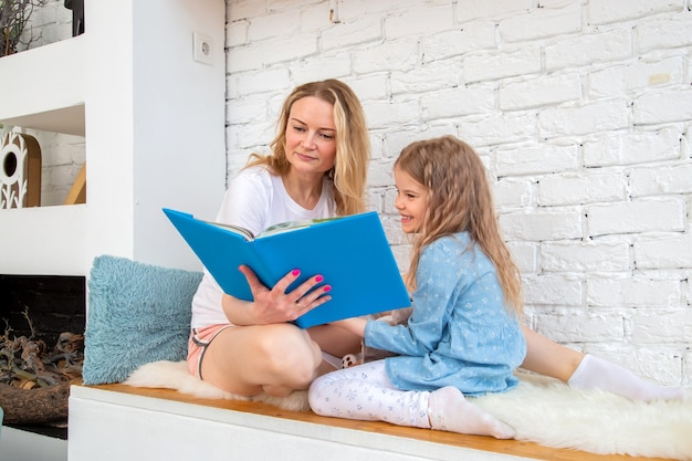 Szczęśliwa mama z córką czyta książkę i uśmiecha się siedząc na podłodze w salonie
