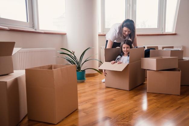 Szczęśliwa mama z córką lub dzieckiem przeprowadzają się w domu i bawią się rozpakowując wszystko w pudełkach