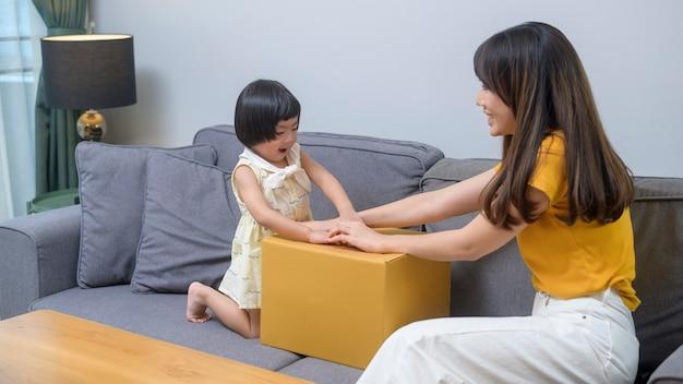 Szczęśliwa mama z córką otwierająca karton w salonie w domu
