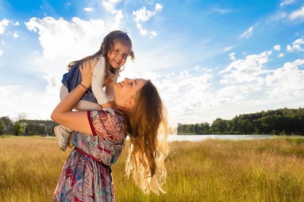 Szczęśliwa mama z córką przeciw pięknemu niebu